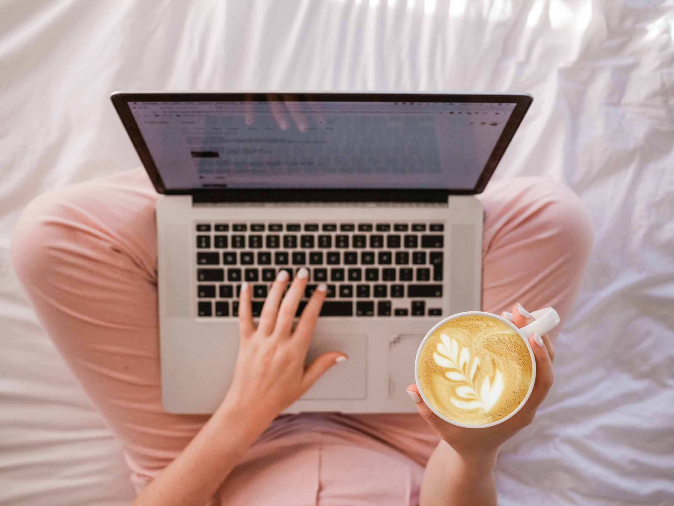girl reading newsletter in laptop computer while holding a latte